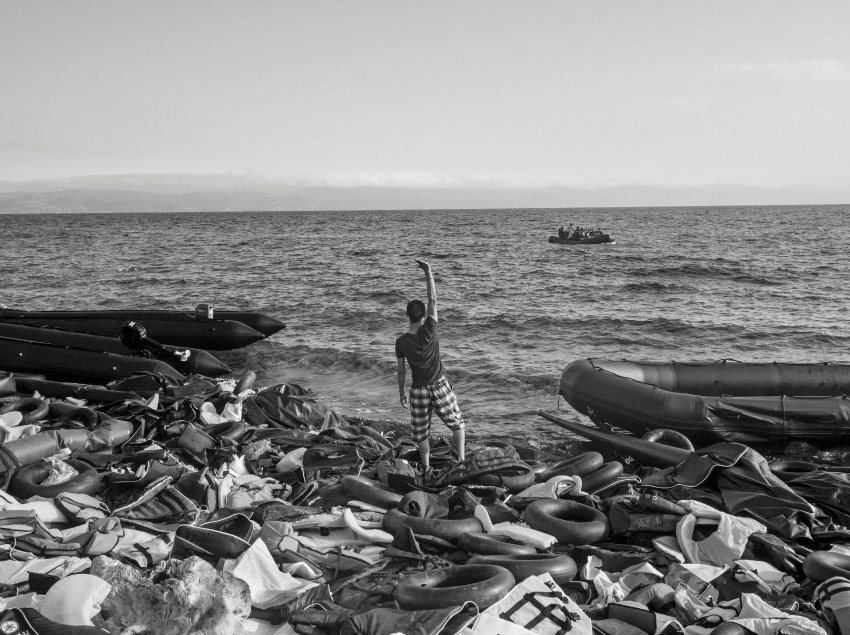 Lesbos Island, Greece. September 29, 2015.A refugee waves to indicate a safe landing area to an approaching inflatable raft as it approaches the shores of Lesbos island in Greece. They had traveled from Assos, Turkey, in inflatable rafts to reach the European Union in the hopes of being granted asylum. (Photo by Moises Saman/MAGNUM)